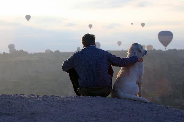 Man met een hond die de vlucht van passagiersballons in cappadocië bekijkt