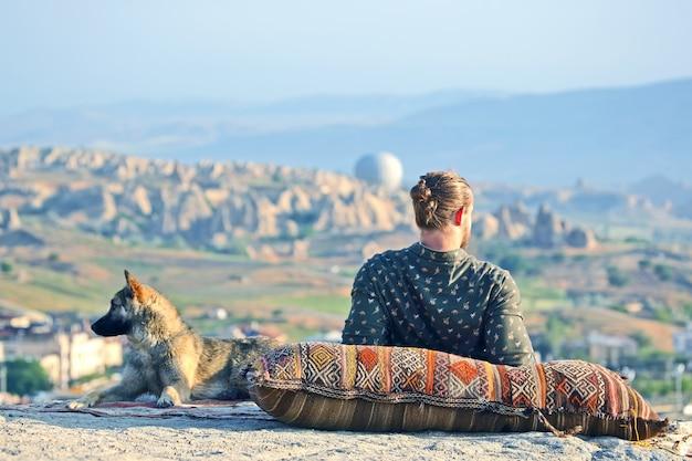 Man met een hond kijken naar de schoonheid van de natuur in cappadocië. kalkoen