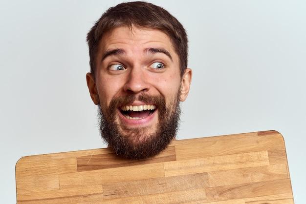 Man met een houten keukenplank en met een schop op een licht