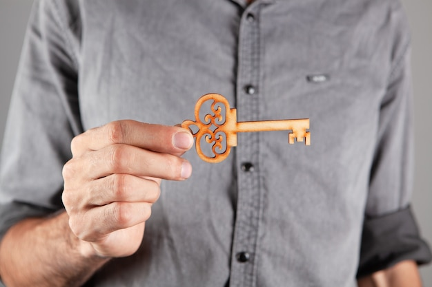 Man met een houten sleutel op grijze achtergrond