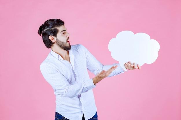 Man met een ideebord in de vorm van een wolk en erop wijst.