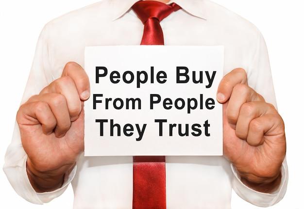 Man met een kaart met een tekst die mensen kopen van mensen die ze vertrouwen.