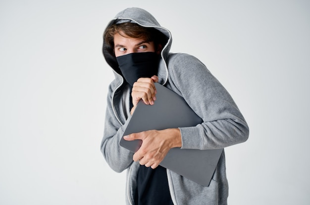Man met een kap op zijn hoofd masker laptop diefstal illegale binnenkomst misdaad.