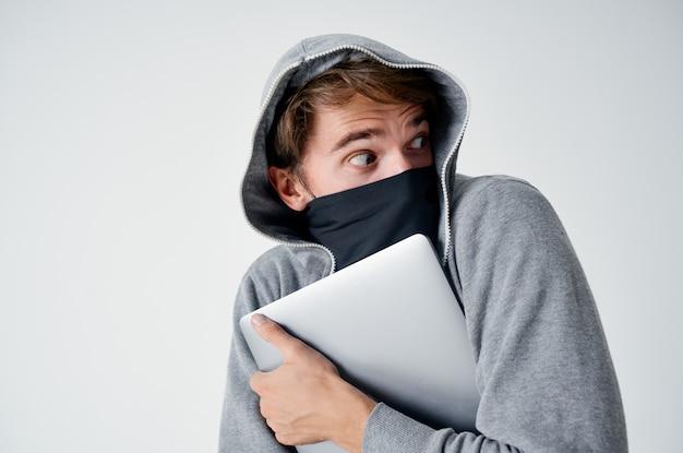 Man met een kap over zijn hoofd masker laptop diefstal illegale binnenkomst criminaliteit