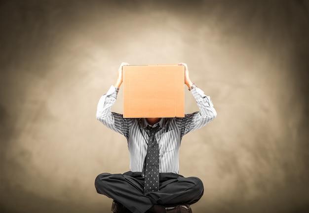 Man met een kartonnen doos op het hoofd