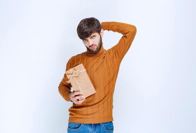 Man met een kartonnen geschenkdoos en kijkt verward en aarzelend.