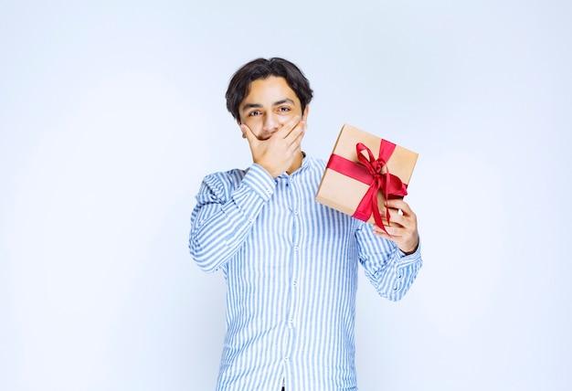 Man met een kartonnen geschenkdoos met rood lint en aarzelend of beschaamd. hoge kwaliteit foto