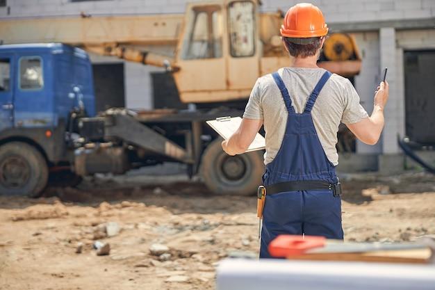 Man met een klembord in zijn hand die op een bouwplaats staat