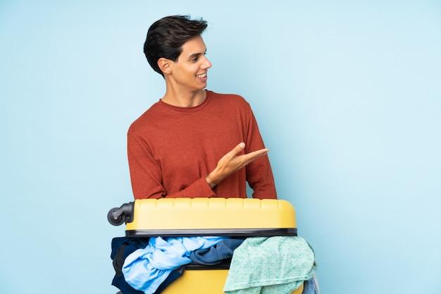 Man met een koffer vol kleren over geïsoleerde blauwe muur die handen naar de zijkant uitstrekt om uit te nodigen te komen