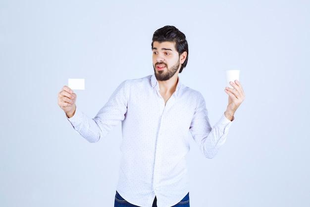 Man met een koffiekopje in de ene hand en zijn visitekaartje in de andere hand
