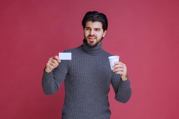 Man met een koffiekopje met zijn factuur of visitekaartje.