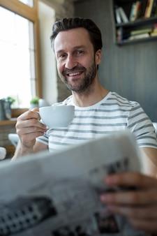 Man met een kopje koffie en het lezen van kranten in de koffiebar