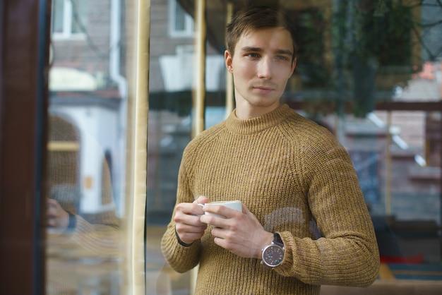 Man met een kopje koffie, in de buurt van het raam