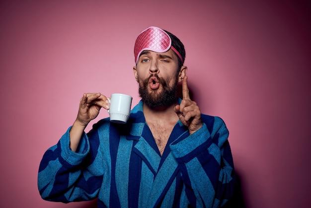 Man met een kopje thee in zijn hand en een roze masker op zijn gezicht op roze