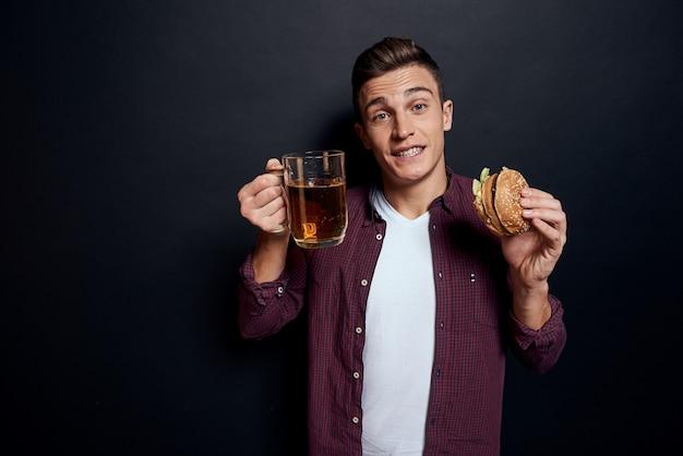 Man met een lade van junkfood: hamburger en frietjes, bier