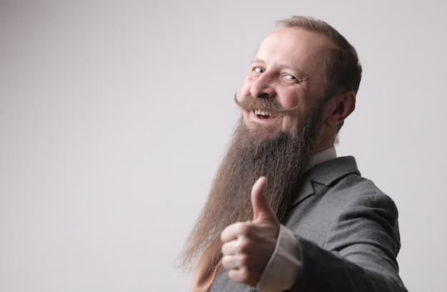 Man met een lange baard en een snor die duimen toont en voor een grijze muur staat