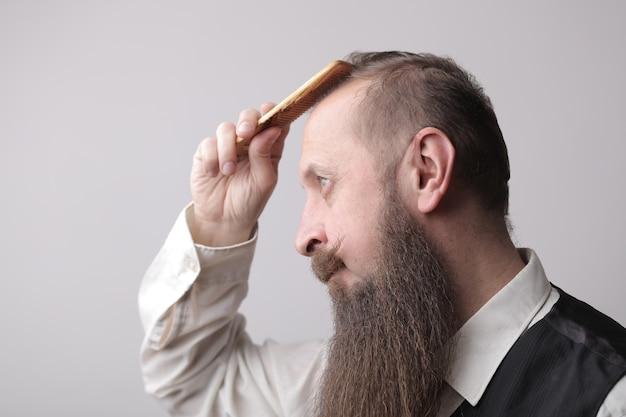 Man met een lange baard en een snor die zijn haar borstelt op een grijze muur