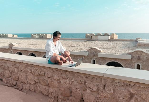 Man met een laptop in zijn handen rusten en werken als freelancer op vakantie