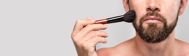 Man met een make-up borstel op zijn gezicht met kopie ruimte