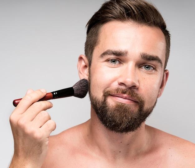 Man met een make-up borstel op zijn gezicht