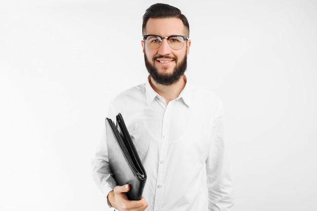 Man met een map in zijn handen, op een witte muur, zakenman met een bril