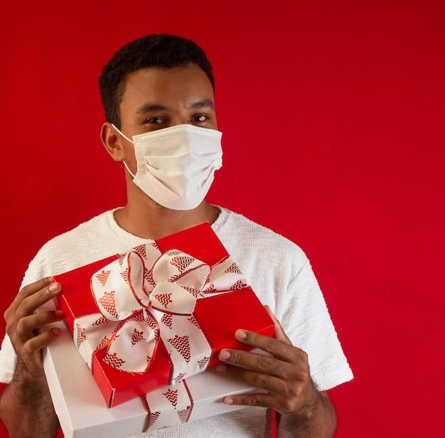 Man met een masker met cadeau in zijn handen