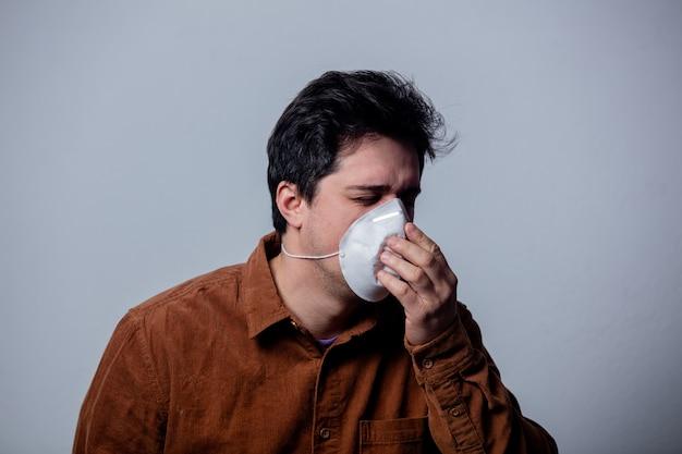 Man met een masker niest