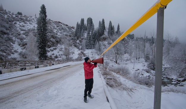 Man met een megafoon in de bergen in de winter