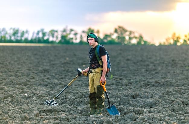 Man met een metaaldetector in het veld. zoeken naar schatten.