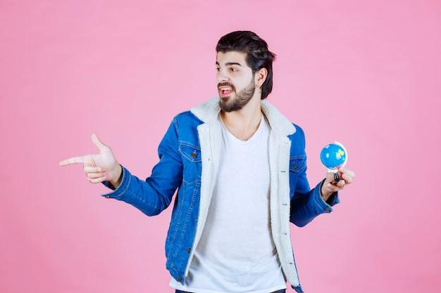 Man met een mini-wereldbol die naar iemand wijst