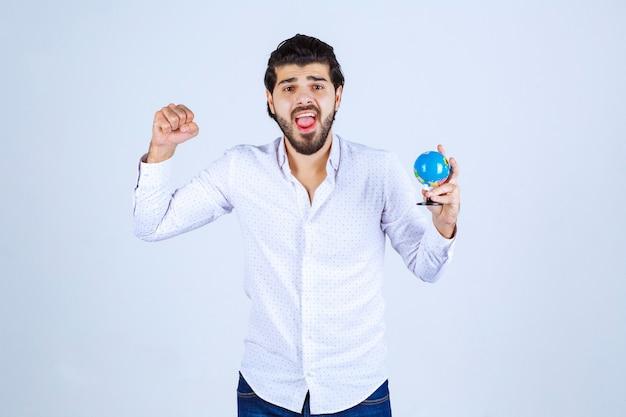 Man met een mini-wereldbol die zijn vuist laat zien