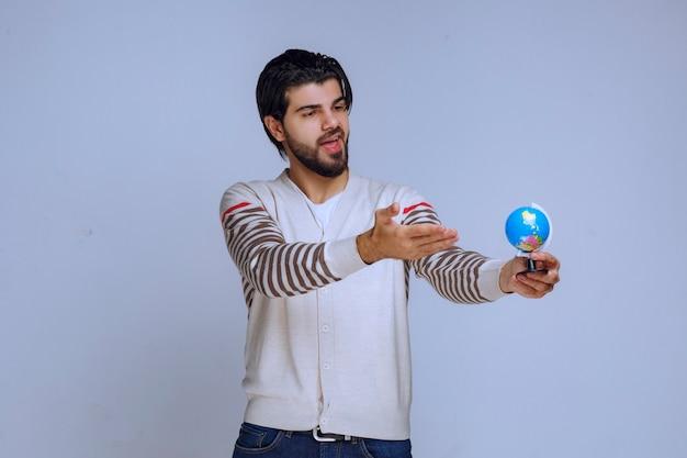 Man met een mini-wereldbol en het lijkt erop dat hij alle locaties en kaart heeft bestudeerd.