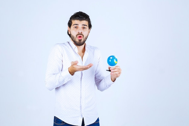 Man met een mini-wereldbol en kijkt verward