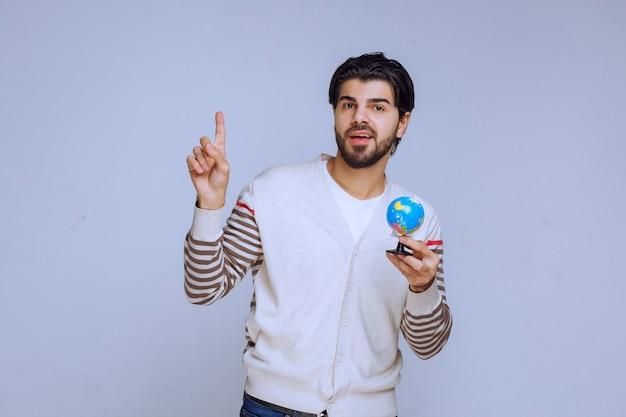 Man met een mini-wereldbol en omhoog.