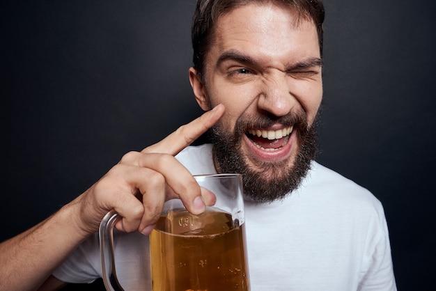 Man met een mok bier in een wit t-shirt emoties levensstijl dronken op een donker