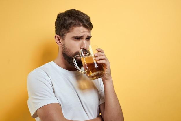 Man met een mok bier plezier alcohol levensstijl wit t-shirt geel en geïsoleerde achtergrond