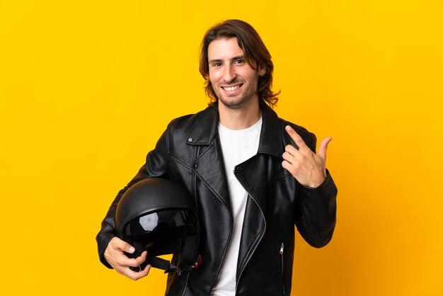 Man met een motorhelm geïsoleerd op geel met een duim omhoog gebaar