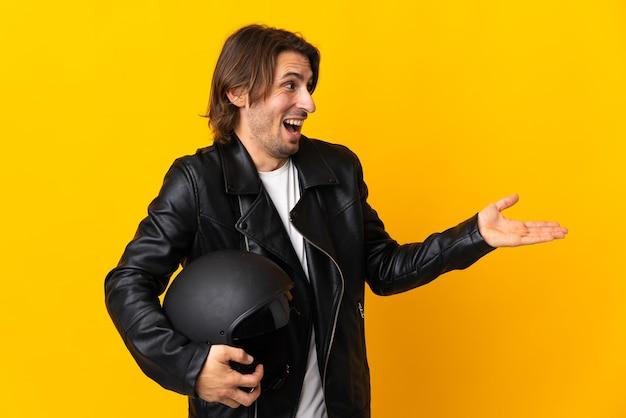 Man met een motorhelm geïsoleerd op geel met verrassing expressie terwijl op zoek naar kant