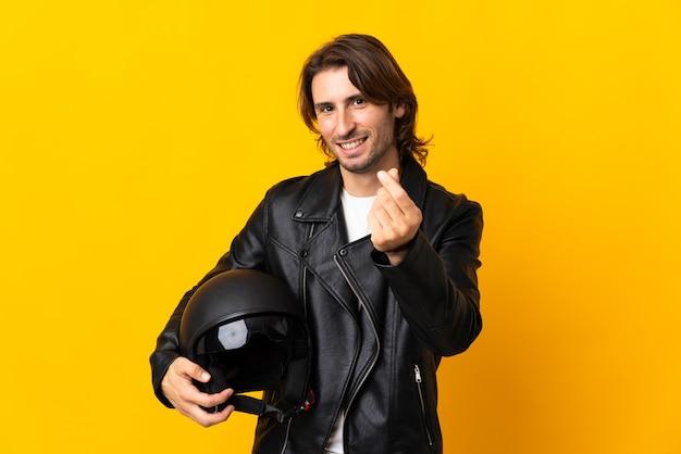 Man met een motorhelm geïsoleerd op gele achtergrond geld gebaar maken