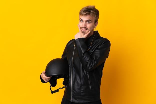 Man met een motorhelm geïsoleerd op gele achtergrond gelukkig en lachend
