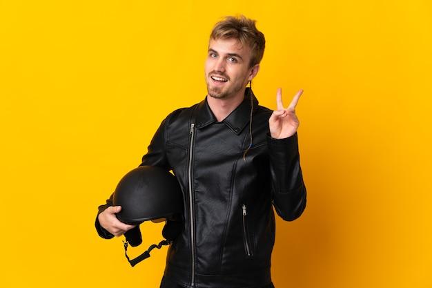 Man met een motorhelm geïsoleerd op gele achtergrond glimlachend en overwinning teken tonen