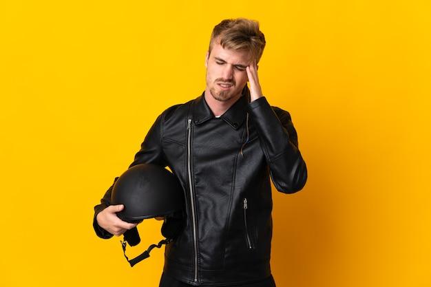 Man met een motorhelm geïsoleerd op gele achtergrond met hoofdpijn