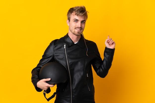 Man met een motorhelm geïsoleerd op gele achtergrond naar achteren