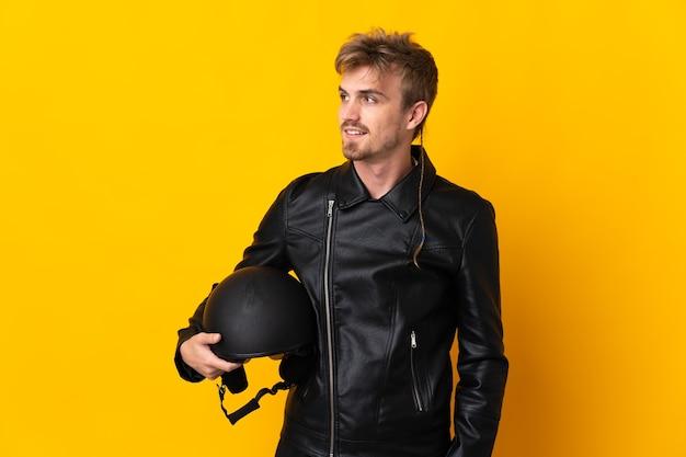 Man met een motorhelm geïsoleerd op gele achtergrond op zoek naar de zijkant en glimlachen
