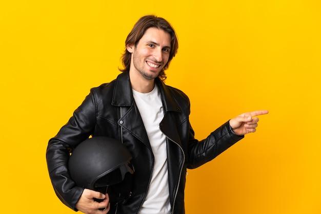 Man met een motorhelm geïsoleerd op gele wijzende vinger naar de zijkant