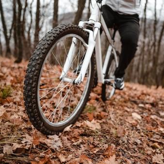 Man met een mountainbike op herfstbladeren