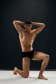 Man met een naakt lichaam in zwart slipje op een donkere achtergrond zit op zijn knie