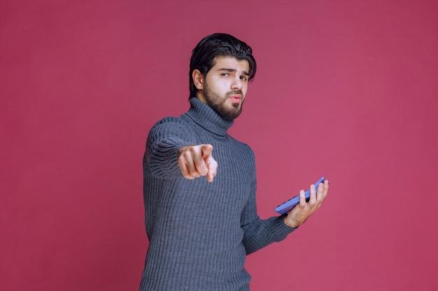 Man met een nieuwe smartphone die naar de klant wijst.