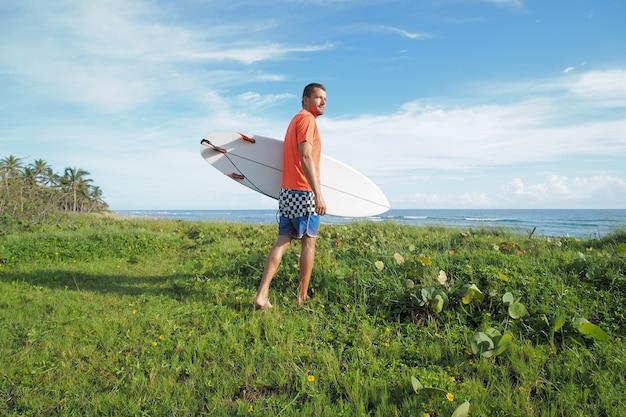Man met een oranje t-shirt en een blauwe korte surfplank die in het gras naast de oceaan loopt