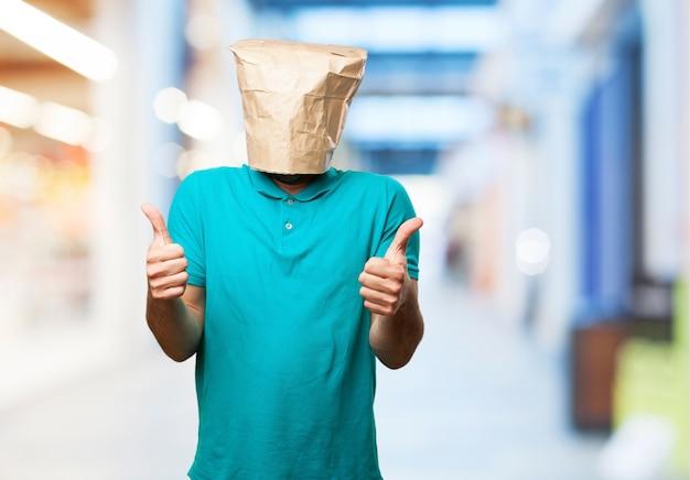 Man met een papieren zak over zijn hoofd met een thumbs up